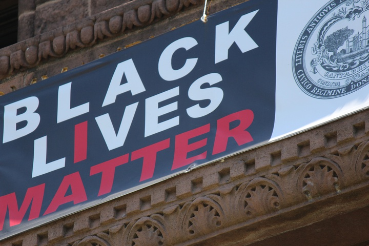 black lives matter banner hanging above the entrance to city hall